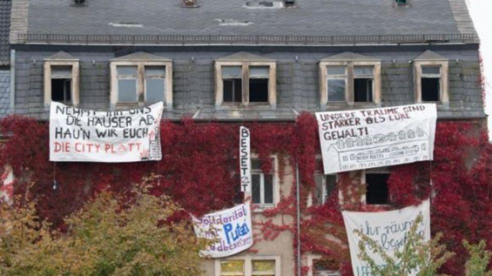 Transparente von Aktivisten hängen an den Fenstern eines leerstehenden Wohnhauses. © Sebastian Kahnert/dpa